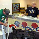 Volunteers remove legs from a pinball game at the National Pinball Museum.