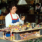 A technician solders parts on a Williams Taxi playfield.